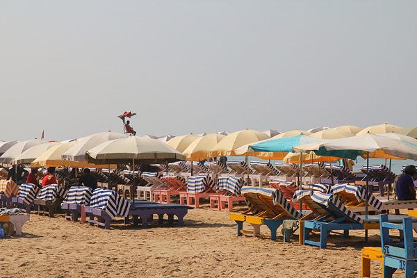 Beach umbrellas stretch the shore of Baga Beach, Goa