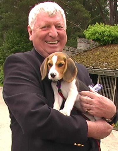 Tom Baker holding a puppy