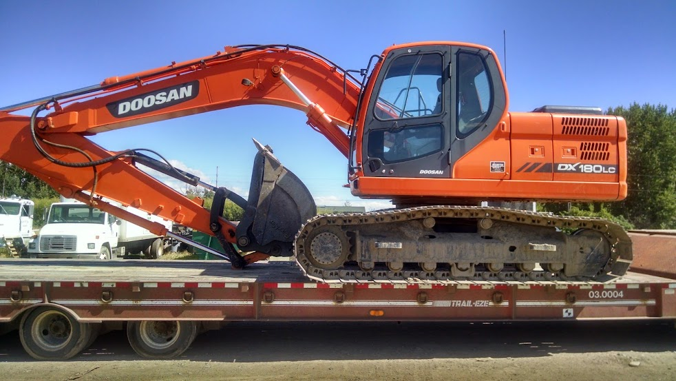 doosan back-hoe loaded on flatbed trailer