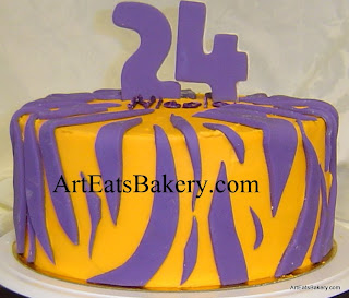 Orange butter cream birthday cake with purple tiger stripes and number 24 topper