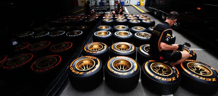 Mecánicos de Lotus inspeccionan los neumáticos Pirelli en el paddock