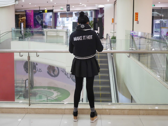 "young woman wearing a coat with the phrase ""MAKE IT HOT"" printed on the back."