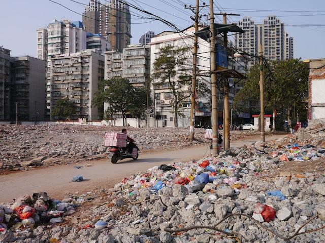 man riding by demolished buildings on Beizheng Street in Changsha