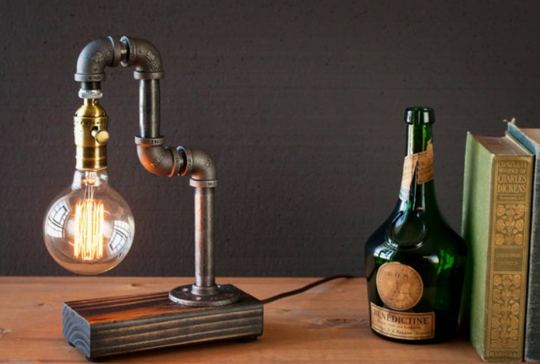Vintage edison style desk light on home office desk with old books and green bottle