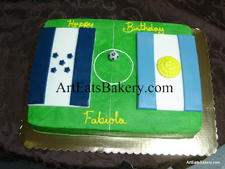 Custom creative soccer field birthday cake design with team flags and soccer ball candle
