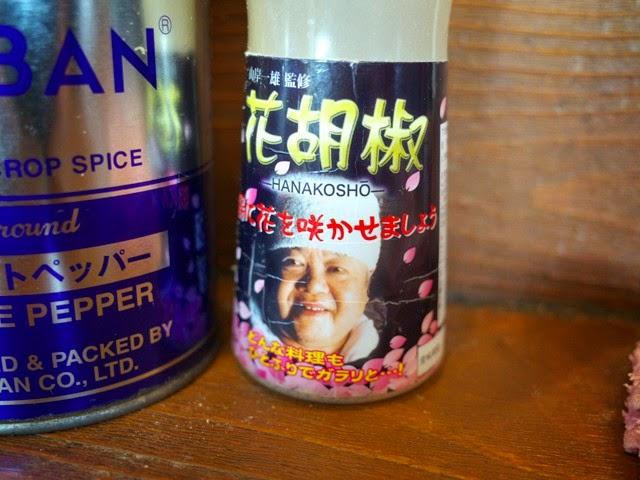 卓上の花胡椒のボトルに描かれた山岸氏の顔写真