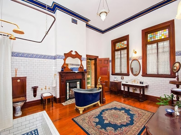 This is a rare Victorian bath room, with Federation features such as the polished wooden floor (not tiled in black and white, Victorian style), relatively simple cornice and wooden window frames with casement windows. The fireplace is Federation style, the mirror above in Art Nouveau style.