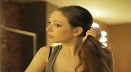 Mujer arreglandose el cabello como sintoma de que le gustas