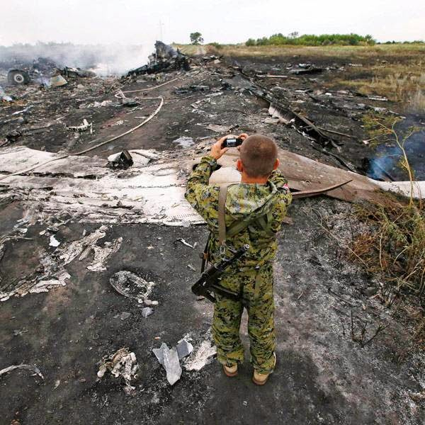 An armed pro-Russian separatist takes pictures at the site of a Malaysia Airlines Boeing 777 plane crash near the settlement of Grabovo in the Donetsk region, July 17, 2014.