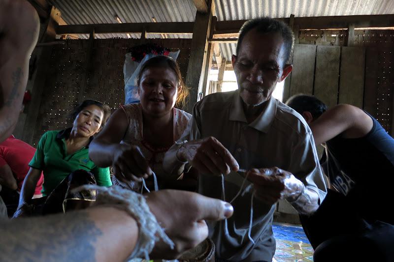 Village chief tying baci bracelets
