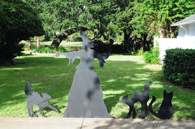 Front view of a witch cutout with three black cats.