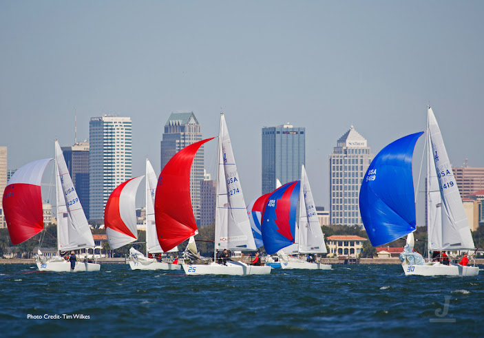 J/24 one-design sailboats- sailing downwind under spinnaker