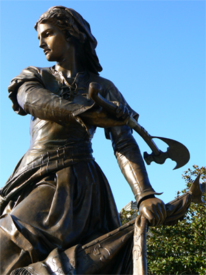 A bronze statue in the open air - a woman in mediaeval European dress holds a battle standard in one hand and wields her hatchet with the other.  Her expression is one of calm determination.