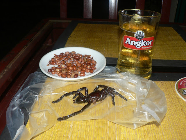 cooked tarantula spider, peanuts, and a glass of beer