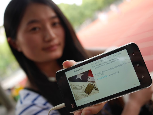 "student showing a Xiaomi smartphone displaying the page for ""facsimile"" in an English language learning app."