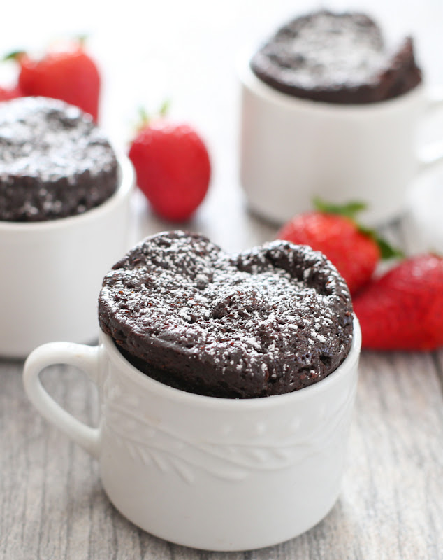 4-ingredient chocolate mug cake in a white mug with two others and fresh strawberries in the background