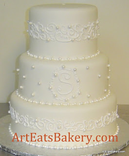 Three tier white fondant custom wedding cake with sugar pearls, monogram and curlicue lace bands design