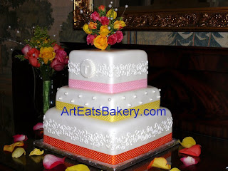Three tier custom square white fondant wedding cake with curlicue band design, pearls, ribbons and monogram