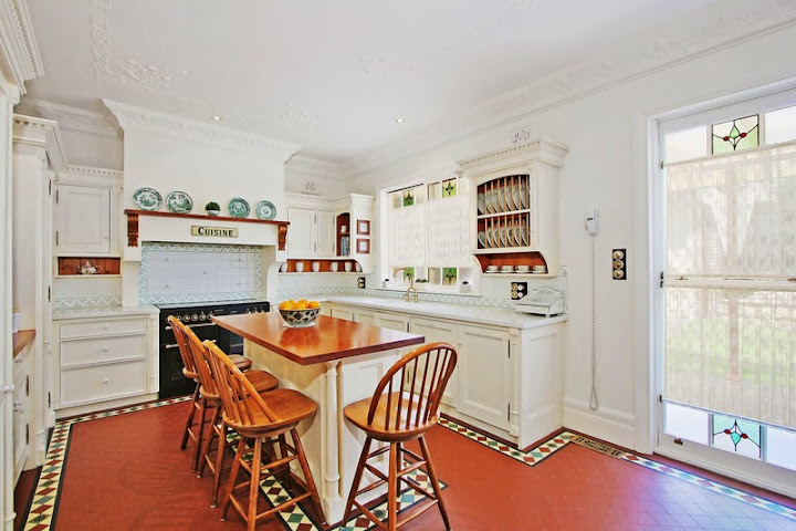 An exquisitely renovated kitchen with many original features, especially the floor, stove and plate display