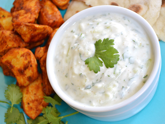 Bowl of Cucumber Raita with chicken bites on the side