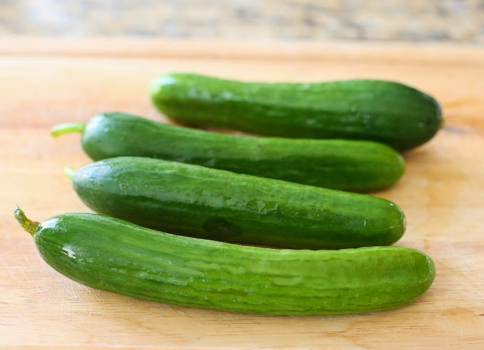 process photo of four cucumbers ready to be smashed