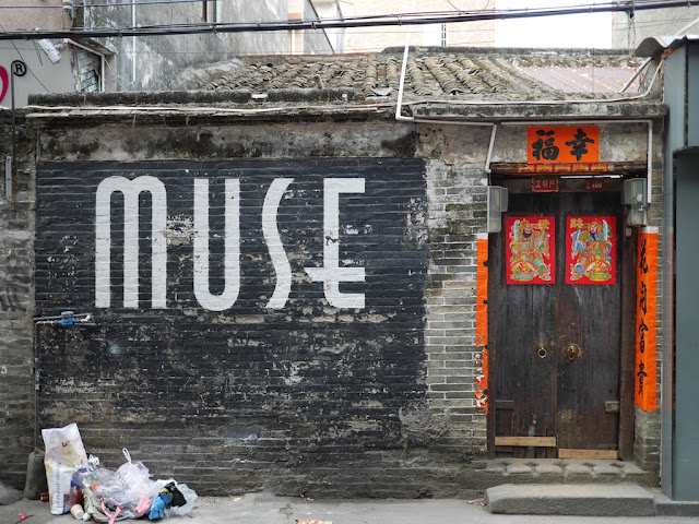 "the word ""MUSE"" written in a large modern script on an old Chinese style building with traditiona; style decorations around its door"