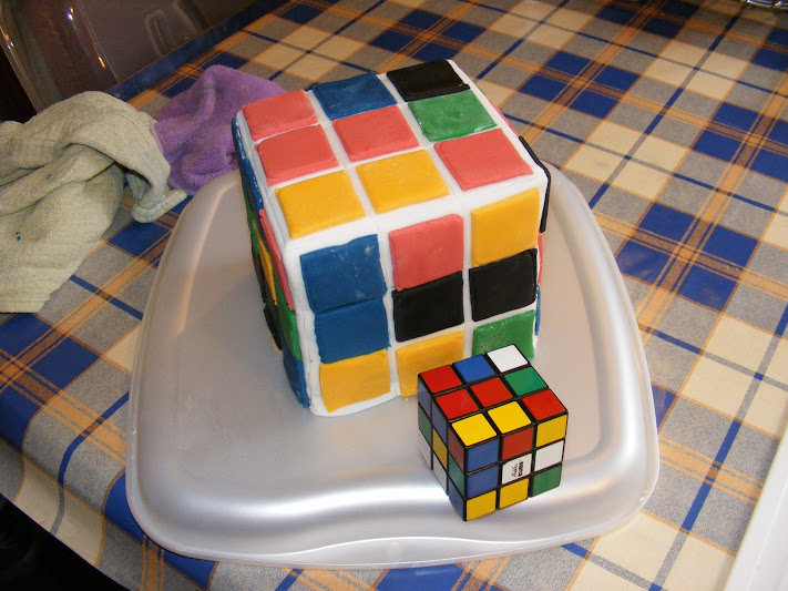 The finished cake, standing alongside the real rubik's cube, used as the model