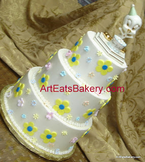 Three tier custom Tweety Bird birthday cake with sugar and fondant flowers and Lenox gold and pastel topper