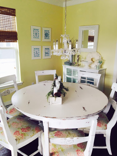 Yellow wall kitchen nook, white table and chairs, light and airy kitchen nook