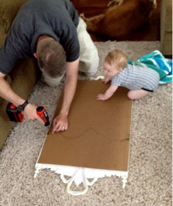 A man taking the backing off of a mirror while a baby crawls nearby