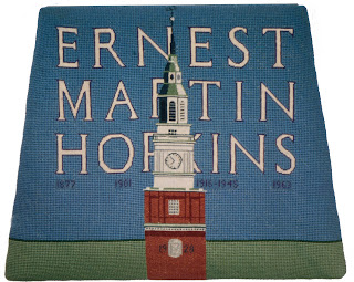 A needlepoint chair cover prominently featuring the name Ernest Martin Hopkins.