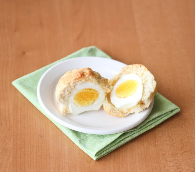 close-up photo of a breakfast muffin sliced in half to show the egg inside