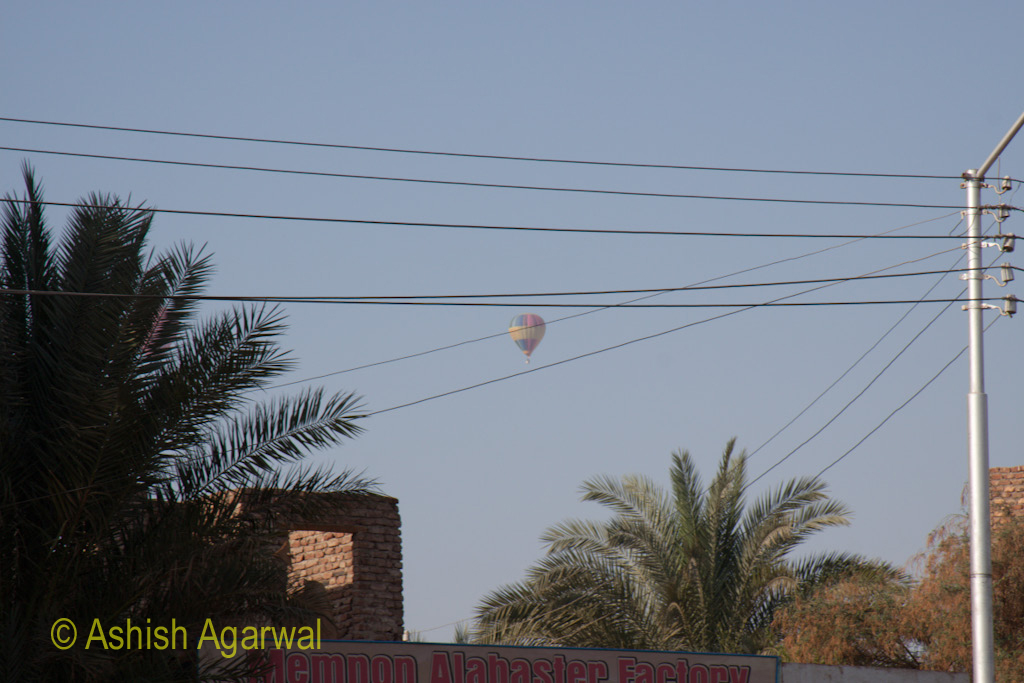 Hot air balloon, visible through some high power wires, over Luxor in Egypt