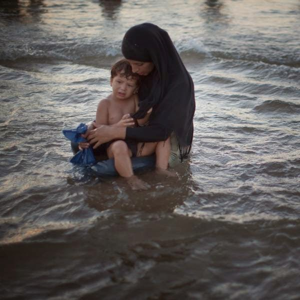 A woman holds her baby as Palestinians enjoy a day at a beach during Eid al-Fitr, in Israel.