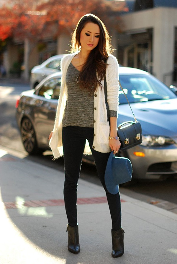 woman in leggings, boots and sweaters carrying a hat