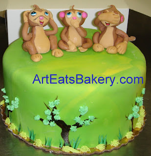 Hear no evil, speak no evil and see no evil monkeys sugar figures on green marbled fondant birthday cake with trees and grass