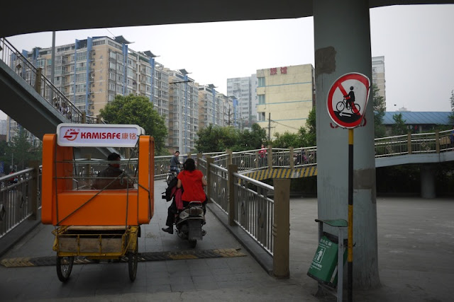 sign with slash through a person on a bike with an arrow below the bike pointing to the left