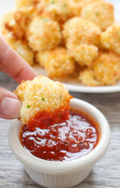 a close-up photo of dipping a parmesan cauliflower bite in a dipping sauce