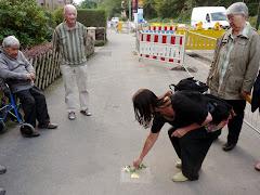 Erika B. legt eine Blume zum Stolperstein.