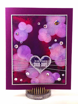 Linda Vich Creates: Valentine Round Up. A sequin-studded, jewel-toned watercolor bokeh background is embellished with a valentine heart strung on silver cords.