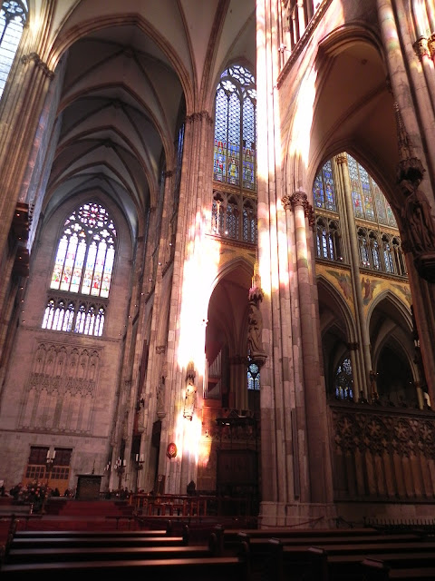 Raios do sol refletindo, através dos vitrais, nas paredes da catedral