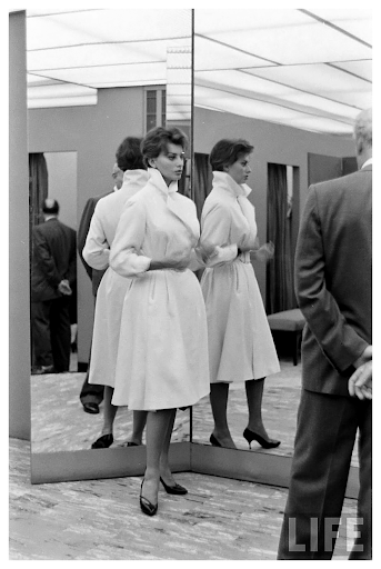 sophia loren trying on a white coat, 1970s.