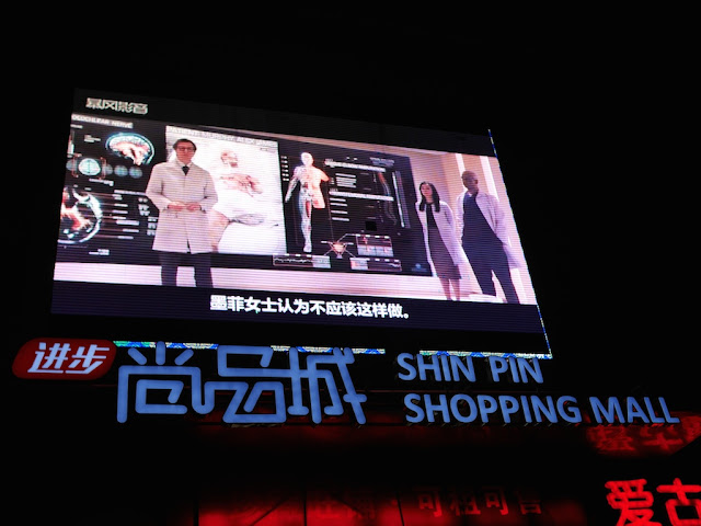 scene from RoboCop (2014) display on a giant screen above a sign for the Shin Pin Shopping Mall in Hengyang