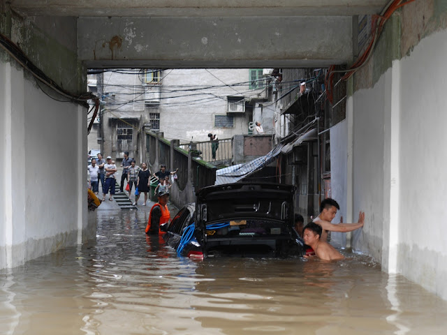 men pushing a car partially submerged in flood waters