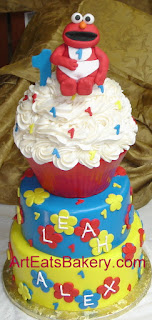 Three tier blue, yellow, and red fondant Elmo 1st birthday cake with giant cupcake top tier