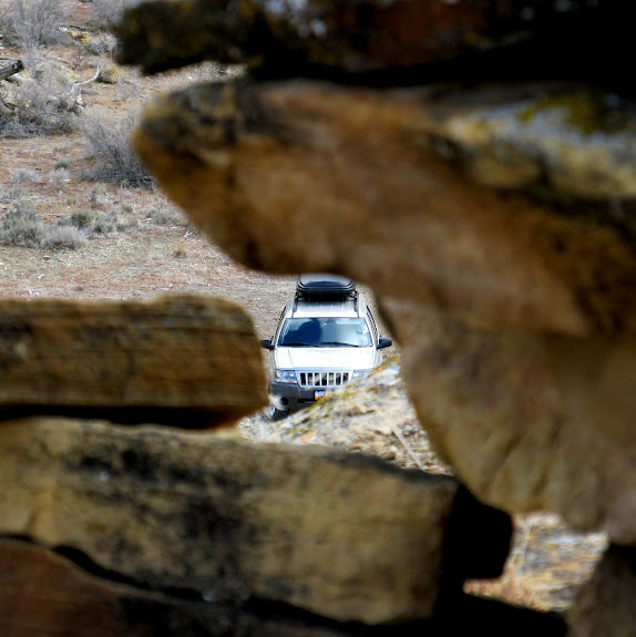 My Grand Cherokee visible through a hole in the wall of a ruin