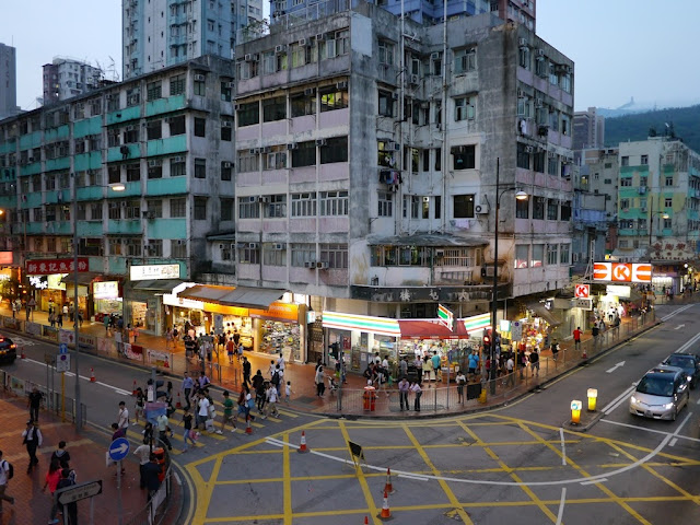 people crossing an intersection with a 7-Eleven in Tsuen Wan, Hong Kong