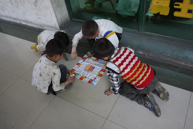 four boys playing a game on the ground in Yinchuan, China