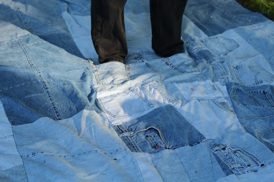 feet in the pockets of a denim quilt