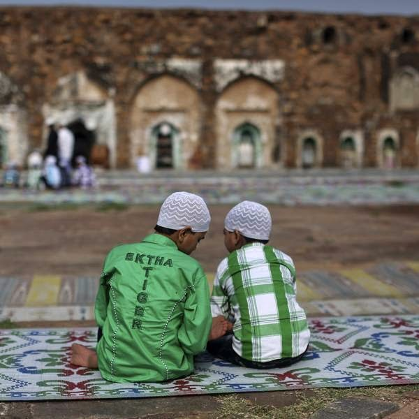 Muslim boys sit at the ruins of the Feroz Shah Kotla mosque before offering prayers on the occasion of Eid-al-Fitr, in New Delhi.